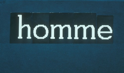 White letters on black paper, tacked onto a blue board, read 'home'