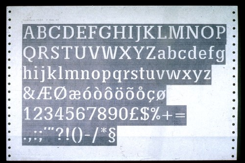Reversed printout on tractor-feed paper shows an alphabet setting of a slabserif typeface