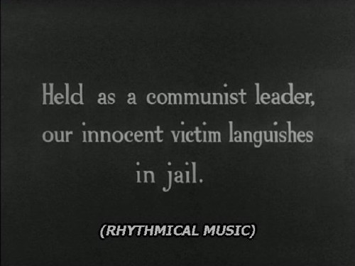 Caption, set in Verdana Italic, reads: (RHYTHMICAL MUSIC). Above it is a hand-lettered title reading: Held as a communist leader, our innocent victim languishes in jail